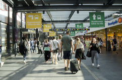 Crowd of people at a train terminal. A crowd of people at a modern train terminal in Sweden. People with luggage are sitting and walking along the building stock photo