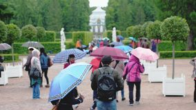 RUSSIA, SAINT PETERSBURG, 20 june 2017, Crowd of people under umbrellas covers in pouring rain in Catherine Park. Crowd of people under umbrellas covers in Stock Images