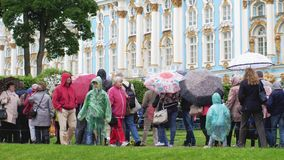 RUSSIA, SAINT PETERSBURG, 20 june 2017, Crowd of people under umbrellas covers in pouring rain stand in line to the. Crowd of people under umbrellas covers in Royalty Free Stock Images