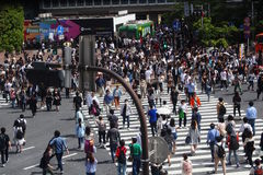 A crowd of people using the pedestrian scramble in front of Tokyo`s Shibuya Station. Royalty Free Stock Photo