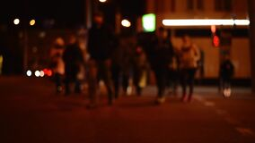 Crowd of people walking along a crosswalk at a traffic light in a night city, slow motion