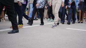 Crowd of people walking on city street. Feet closeup stock video
