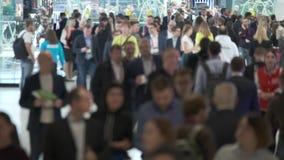 Crowd of people walking indoors, the foreground is defocused,