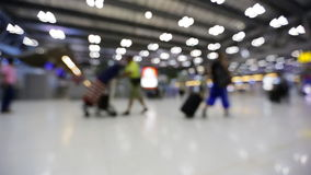 Crowd of people walking with luggage in the international airport, de-focused scene stock footage