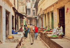 Crowd of people walking on narrow street with food sellers and small vegetable stores Royalty Free Stock Images
