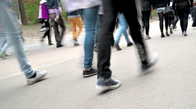 Crowd of people walking on road. Legs and feet of crowd of people walking on road Royalty Free Stock Photo
