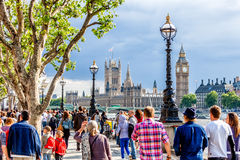 Crowd of people walking on the southern bank of the River Thames, London Royalty Free Stock Photos