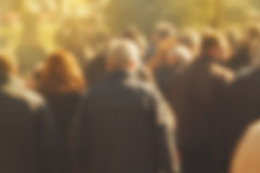 Crowd of People Walking On the Street in Bokeh. Unrecognizable group of men and women as blur urban background Stock Photo