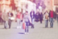 Crowd of People Walking On the Street in Bokeh. Unrecognizable group of men and women with shoppingbags as blur urban background Royalty Free Stock Images
