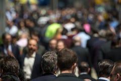 Crowd of people walking on street sidewalk Stock Images