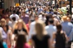 Crowd of people walking on street sidewalk Royalty Free Stock Images