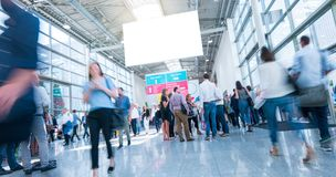 Crowd of people walking a a trade show. Crowd of business people rushing in trade show hall, including copy space banner. ideal for websites and magazines stock photography