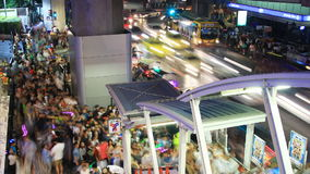 Crowd of people walking with traffic jam at Siam Center, Bangkok stock footage