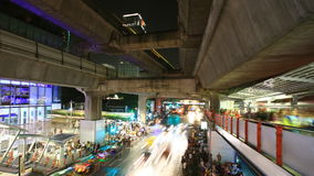 Crowd of people walking with traffic jam at Siam Center, Bangkok stock video footage