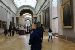 Crowd of people wandering through hallways, admiring masterpieces,The Louvre,Paris,France,2016. Crowd of visitors strolling down long hallways as they admire Stock Image
