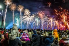 Crowd of people are watching to fireworks. Celebration of Latvia 100th anniversary. 18.11.2018. RIGA, LATVIA. Staro Riga festival of light and Fireworks, light stock photography