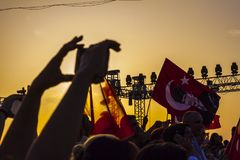 Turkish crowd in the sunset commemorating liberation from greeks. A crowd of people is waving many turkish flags in the sunset in Izmir to commemorate the royalty free stock photo