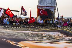 Turkish people commemorating liberation of Izmir from greeks. A crowd of people is waving turkish flags on the wind and a very big flag with the portrait of royalty free stock image