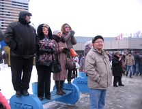 A crowd of people in the winter standing on a bench waiting for the event watching stock image