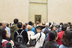 Crowd photographing Mona Lisa. A crowd in front of Mona Lisa painting in the Louvre, Paris Royalty Free Stock Image