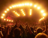 Crowd at rock concert in front of illuminated stage. Silhouettes of cheering people at rock concert in front of stage illuminated with spotlights Stock Photography