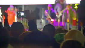 Crowd on Rock Concert. Crowd people dancing Rock concert, weighed, applauds, raises his hands up and photographed, filmed concert on the phones and smartphones stock video footage