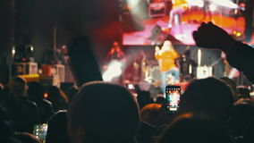 Crowd on Rock Concert. Crowd people dancing Rock concert, weighed, applauds, raises his hands up and photographed, filmed concert on the phones and smartphones stock video