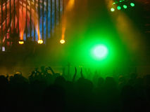 Crowd at rock concert. Silhouettes of cheering people backlit by big green spotlight at rock concert in front of illuminated stage Stock Photos