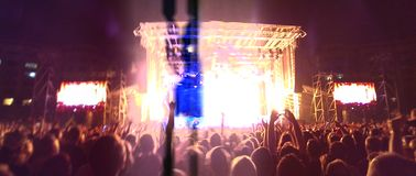 Crowd at rock concert. Wide angle view of crowd of people at rock concert with illuminated stage in background royalty free stock photo