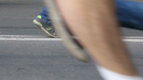 The crowd is running on asphalt in running shoes from left to right. stock video