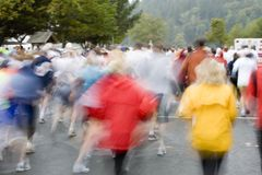 Crowd running in rain. Large crowd of spectators and runners at a sporting event in the rain.  Motion blur Royalty Free Stock Photo