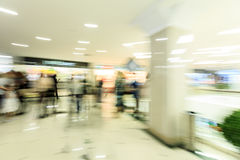 Crowd rushing inside a modern wide bright mall hall with boutiques, glass display windows, people in motion blur Stock Photos