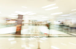Crowd rushing inside a modern wide bright mall hall with boutiques, glass display windows, people in motion blur Royalty Free Stock Images