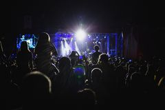 The crowd of spectators in front of the concert stage. Light from searchlights Royalty Free Stock Images