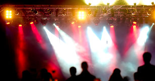 Crowd and spotlights. Crowd of people in front of spotlights at a concert royalty free stock photos