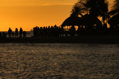 Crowd in sunset. People on the beach on pier on Caribbean Sea coast Stock Photography