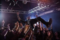 Crowd surfing at a concert. In nightclub royalty free stock photos