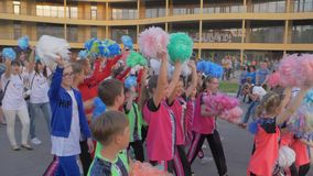 Crowd of teenagers in bright costumes waving pompoms on hands during summer festival on city street on holiday. Kherson, Ukraine - May 20, 2019: Festival stock video footage