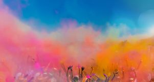 Crowd throwing bright coloured powder paint in the air. Holi Festival Dahan stock image