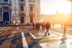 Crowd of tourist people walking in center of old town near Duomo in Milan, Italy at sunset time. Stock Photos
