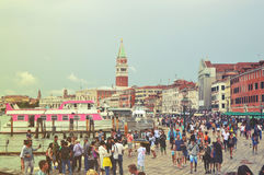 Crowd of tourist in Venice promenade with St Mark tower bell church, Venice, Italy. Vintage filte stock image