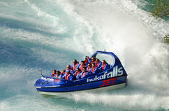 Crowd  tourists experiencing best of New Zealand in scenic Waikato River. A jet boat speeds towards the waterfalls and the crowd of thrill seekers on board get