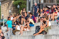 Crowd of tourists sit on the National Palace stairs in Barcelona Stock Photos