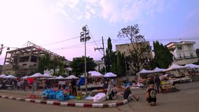 Crowd of traveler are walking on walking street and street food on Thanalai Road and 75 Anniversary Flag and Lamp Park. Chiang Rai, Thailand - April 22, 2017 stock video footage