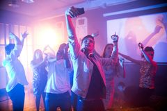 Teenager Taking Selfie on Dance Floor. Crowd of trendy young people dancing in nightclub and enjoying party, focus on  handsome young men taking selfie on dance Stock Photography
