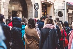 Crowd of unrecognizable people wait in line in a urban setting queue of people royalty free stock photos