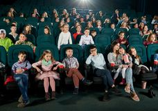 Crowd of viewers sitting in movie theatre and watching cartoon. Front view of many children and teenagers sitting in movie theatre and enjoying cartoon. Cute royalty free stock images