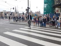 Crowd waits on city intersection on Damrak for lights to change Stock Photos