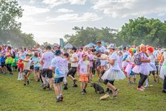 Crowd Warming Up Prior To Color Frenzy Fun Run. MACKAY. QUEENSLAND, AUSTRALIA - JUNE 2019: Unidentified people splashed with colored power warming up prior to a royalty free stock image