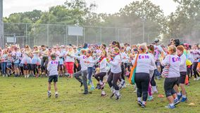 Crowd Warming Up Prior To Color Frenzy Fun Run. MACKAY. QUEENSLAND, AUSTRALIA - JUNE 2019: Unidentified people splashed with colored power warming up prior to a stock image